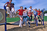 Fifth grade students jumping off playground equipment. Oregon.