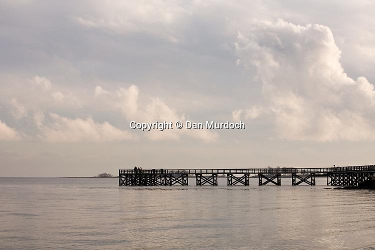 Fishing pier under cloudy skies