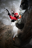 Ice climber in red jacket climbs colourful underground ice structure, Sweden