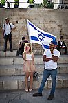 An Israeli woman holds a flag outside Damascus gate in Jerusalem Wednesday May 28 2014, during festivities marking Jerusalem day. The Day marks the reunification of Jerusalem following the 1967 Six Day War when Israel captured the Arab part of the city from Jordan. Photo By Eyal Warshavsky