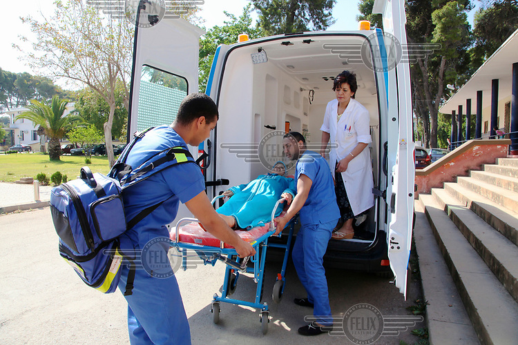 Medics transfer a pregnant woman from an ambulance into the neonatology unit at the Ghassani Hospital.
