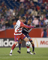 FC Dallas forward Kenny Cooper (33) attempts to control ball as New England Revolution defender Darrius Barnes (25) defends. The New England Revolution defeated FC Dallas, 2-1, at Gillette Stadium on April 4, 2009. Photo by Andrew Katsampes /isiphotos.com