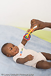 5 month old baby boy African American vertical on back happy reaching to grasp toy his mother holds