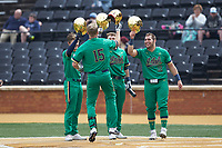 Eric Gilgenbach (15) of the Notre Dame Fighting Irish is greeted at home plate by teammates Ryan Cole, Carter Putz, and Niko Kavadas (12) after hitting a 3-run home run against the Wake Forest Demon Deacons at David F. Couch Ballpark on March 10, 2019 in  Winston-Salem, North Carolina. The Demon Deacons defeated the Fighting Irish 7-4 in game one of a double-header.  (Brian Westerholt/Four Seam Images)