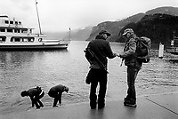 "Switzerland. Canton Schwyz. Brunnen. Two men, both members of riflemen's association, talk together while their wifes clean their muddy shoes in the water of Lake Lucene. Both men carry semi-automatic assault rifles SG 550. Both couples have just returned by boat from  the Rütlischiessen (Rütli shooting). Rütli or Grütli is a mountain meadow overlooking the lake Lucerne where the oath of the Rütlischwur for the forming of the Old Swiss Confederacy is said to have occurred as the legendary turning-point in the pursuit of independence. To commemorate this historic event, the riflemen's association of Lucerne organized the Rütli rifle match (Rütlischiessen) in 1862. It is held every year on the Wednesday before Martinmas (Saint Martin's Day). The SG 550 is an assault rifle manufactured by Swiss Arms AG (formerly Schweizerische Industrie Gesellschaft) of Neuhausen, Switzerland. ""SG"" is an abbreviation for Sturmgewehr, or ""assault rifle"". The rifle is based on the earlier 5.56mm SG 540 and is also known as the Fass 90 or Stgw 90. An assault rifle is a selective-fire rifle that uses an intermediate cartridge and a detachable magazine. Brunnen is a resort on Lake Lucerne. Lake Lucerne (German: Vierwaldstättersee, literally ""Lake of the Four Forested Settlements"", French: lac des Quatre-Cantons, Italian: lago dei Quattro Cantoni) is a lake in central Switzerland and the fourth largest in the country. 8.11.2017 © 2017 Didier Ruef"