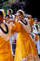 Young woman performing hula auwana (modern hula) with her hula halau (hula school)