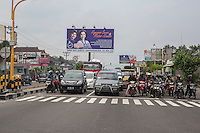 Yogyakarta, Java, Indonesia.  Motorbikes and Cars at Intersection, Waiting for Light to Change.