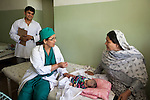 5 June 2013, Kholm District Hospital, Mazar-i-Sharif, Balkh Province, Afghanistan.    Six day old Asma, lies on her bed as Dr Maliha Aziz , Chief Medical Officer at the Kholm District Hospital outside Mazar-i-Sharif attends to her with the other resident doctor Saber Zahier. Grand mother Zeba is looking on.  The hospital which has 54 beds and before 2004 was only a clinic is funded by the Strengthening Health Activities for Rural Poor Project (SHARP). SHARP aims to improve the health and nutrition status of Afghans, focusing especially on women and children and the underserved areas of the country. Already remarkable progress has been made in the reduction of infant and under five mortality as well as pregnancy related mortality. With World Bank support in 11 provinces the number of health clinics has nearly tripled from 148 to 432 and about 85% of the population now lives in districts which now have service providers to deliver a basic package of health service.  The project supports Afghanistan's Health and Nutrition Sector Strategy  which is the governments blueprint for the health sector program for the period 2008-13. Picture by Graham Crouch/World Bank.