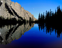 A perfect reflection in Willow Lake at sunrise, with the moon setting to the west.