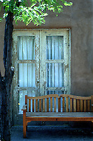 A weathered window on an adobe building and a bench in a courtyard in Santa Fe, New Mexico.