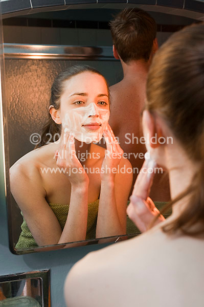 Reflection of young woman washing her face in bathroom mirror