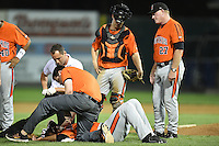 Aberdeen IronBirds trainer Chris Poole checks on pitcher Ivan Hernandez (38) after getting hit in the head by a broken bat as manager Matt Merullo (27) looks on during a game against the Williamsport Crosscutters on August 4, 2014 at Bowman Field in Williamsport, Pennsylvania.  Aberdeen defeated Williamsport 6-3.  (Mike Janes/Four Seam Images)