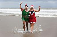 Two women in an elf and a Santa fancy dress