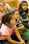 Education preschoool children ages 3-5 group of children seated on rug listening to story read by teacher (not visible) vertical