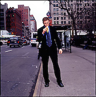 Man in suit standing on sidewalk eating a banana<br />