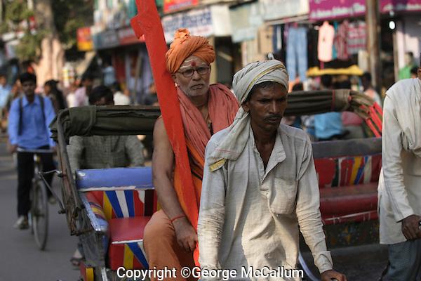 Rickshaw wallah or puller with Sadhu or holy man in back. Varanasi, Uttar Pradesh, India