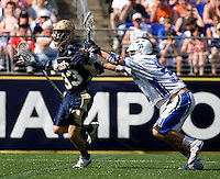 David Lawson (31) of Duke checks David Earl (33) of Notre Dame during the NCAA Men's Lacrosse Championship held at M&T Stadium in Baltimore, MD.  Duke defeated Notre Dame, 6-5, to win the title in overtime.