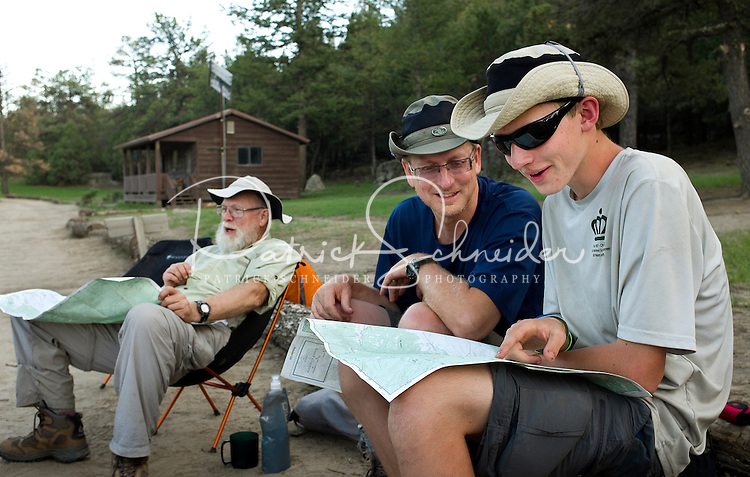 Photo story of Philmont Scout Ranch in Cimarron, New Mexico, taken during a Boy Scout Troop backpack trip in the summer of 2013. Photo is part of a comprehensive picture package which shows in-depth photography of a BSA Ventures crew on a trek.  In this photo adult advisors  and youth crew members look over maps, as the Venture crew worked to make plans for their next days hike in the backcountry at Philmont Scout Ranch.   <br /> <br /> The  Photo by travel photograph: PatrickschneiderPhoto.com