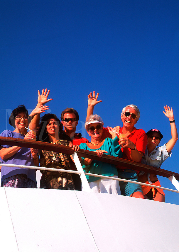 People on deck waving as cruise ship leaves dock