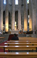 A dark lone man sitting in a church. Barcelona, Catalonia, Spain.