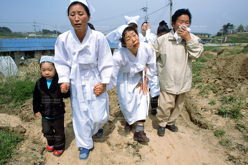 Korea. South Korea. Gimje area. Wonpyong. Funeral ceremony for an old man who died a few days ago. Traditional korean burial and burial service. Family sheds tears. © 2002 Didier Ruef
