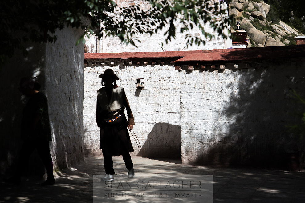 A pilgrim walks through Sera monastery, located in the north of Lhasa. The monastery is one of the most important 'university monasteries' in Tibet and is home to hundreds of monks, famed for their heated debates which are part of their training and study of buddhist doctrines.