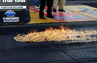 Oct. 14, 2011; Chandler, AZ, USA; Raw fuel burns in flames on the track surface after NHRA top fuel dragster driver Cory McClenathan blew a fuel hose during qualifying for the Arizona Nationals at Firebird International Raceway. Mandatory Credit: Mark J. Rebilas-
