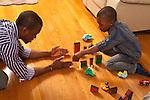 4 year old boy playing with father building road with blocks together talking