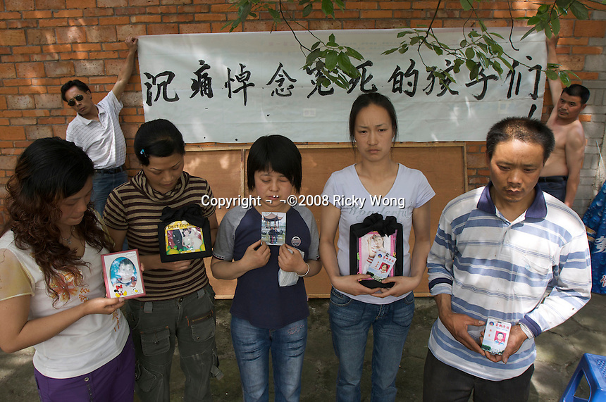 Desperate parents pose for pictures with photos of their died single child. First row: Fan Guanglan, 37 (Zhang Wenxin, 10),   Xiong Ying, 32 (Liu Xingyingyue, 10), Chen Yu, 35 (Huang Qingfeng, 13), Liu Xiaoying, 32 (Bi Yuexing, 13) and Zhang Yingui, 40 (Zhang Ao, 12). Parents of the children victims prepare a petition banner accusing the poor quality of the school building which collapsed during the earthquake causing about 200 out of 309 children die in Fuxin town, Mianzhu city. 18 May, 2008, the sixth day after the 7.8 magnitude earthquake in Mianzhu, Sichuan, China. The earthquake happened at 14:28pm on 12 May 2008, with the epicenter in Wenchuan County, about 159km NW of Chengdu, Sichuan, China..18 May 2008