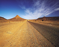 Lonely road penetrating sandy rocky hills in the eastern Atlas Mountains, southern Morocc