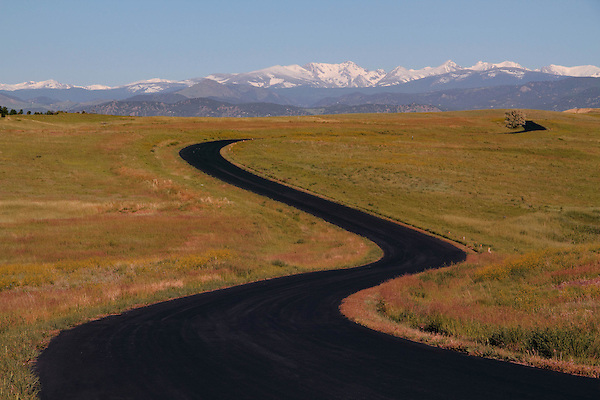 Winding paved road in the autumn foothills with the Indian Peaks Wilderness Area behind, Boulder, Colorado, USA