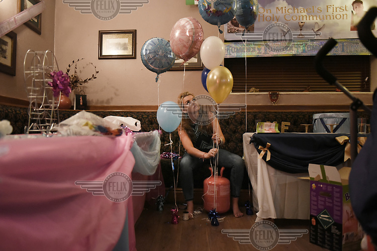 Irish Traveller Precious Sheridan prepares balloons for her son Michael's First Holy Communion celebration held in the The Pressers Arms public house.