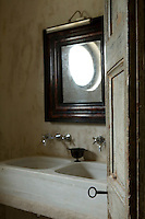 A view into a simple bathroom reveals a wooden mirror hanging over a double basin arrangement.