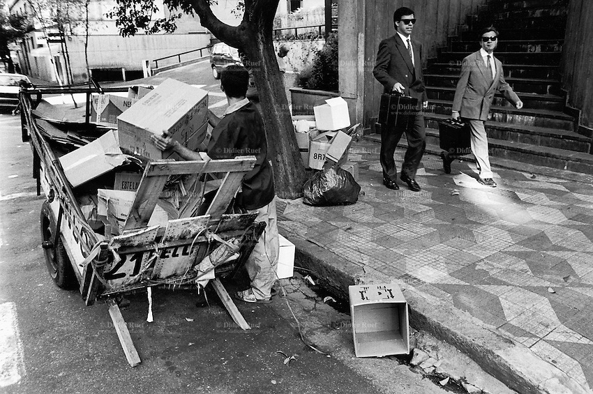 """Brazil. Sao Paulo state. Sao Paulo. Rogerio is 21 years old. He is a poor man who lives in the street. He stands close to his cart which belongs to """"El Gringo"""", owner of a buy-off center for recycled products. The """"catadores"""" are men who collect paper, plastics, metals, bottles ... in order to sell these items as recycled materials and make a living. Waste collector. Two white collar men with business suits, ties, sunglasses and attaché cases walk on the sidewalk. © 1994 Didier Ruef .."""