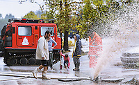 People look on as members of the emrgency services pump out flood water in Nea Mihaniona