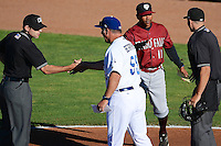 Ogden Raptors manager Damon Berryhill #55 and Idaho Falls Chukars manager Omar Ramirez #11 meet with umpires Tyler Ferguson and Alex Mackay prior to the Pioneer League game at Lindquist Field on June 22, 2013 in Ogden, Utah.  (Stephen Smith/Four Seam Images)