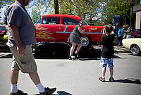 """A woman skating along Second Avenue in Sandpoint, ID stops to have her photograph taken in front of Greg Lassen's hot rod, """"The Cherry"""" while another man walks past on Saturday, May 15. People were allowed to wander throughout six square blocks of the downtown area and enjoy the retro cars and trucks. .. (©Matt Mills McKnight/2010)"""