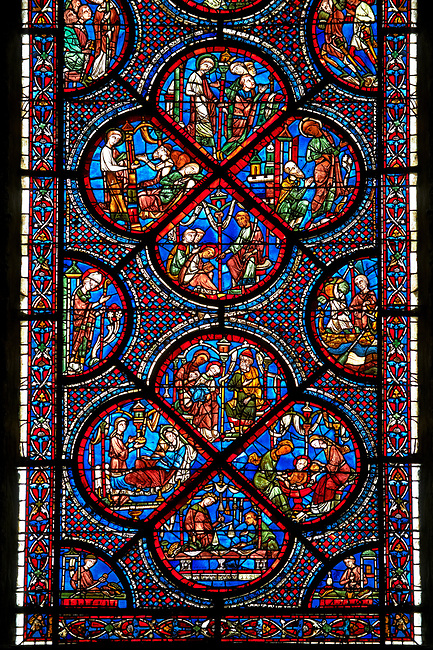 Medieval Windows  of the Gothic Cathedral of Chartres, France, dedicated to the life an miracles of St Nicholas. A UNESCO World Heritage Site. Bottom corners, left shows a belt seller, right a merchant. Centre panel, bottom shows a merchant with scales, left birth of St Nicholas, left the miracles of the first bath of St Nicholas, top The infant St Nicholas refuses his mother's milk except on mondays and fridays..Centre panel above ,  bottom shows The young St Nicholas does well at school, left Nicholas secretly gives gold to an old man to save his daughters , right The old man tries to thank Nicholas, who humbly flees from him, top Nicholas is chosen to be the new Bishop of Myra.