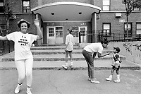 """USA. New York City. Spanish Harlem. Nina (L) wears a self-designed t-shirt with the written words """" I love men, money, sex """". She also dances on the sidewalk. Sala (C), her daughter, stands on the staircase. Bente (CR), her niece, plays with Papo (R). The Puerto Rican family lives below the poverty line and receives public assistance (AFDC, Home Relief, Supplemental Security Income and Medicaid). The family resides in units managed by the New York City Housing Authority (NYCHA) which provides housing for low income residents. NYCHA administers rental apartments in facilities, popularly known as """"projects"""". Spanish Harlem, also known as El Barrio and East Harlem, is a low income neighborhood in Harlem area. Spanish Harlem is one of the largest predominantly Latino communities in New York City. 26.06.88 © 1988 Didier Ruef .."""
