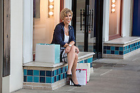 Attractive female shopper with colorful shopping bags sits and takes a break from a busy day shopping at an Austin shopping mall.