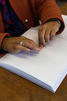 South Africa, Cape Town.  Editor Using the Fingertips to Read a Braille Student Workbook.  Athlone School for the Blind.