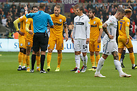 Tom Clarke of Preston North End (C) protests to referee James Linington for awarding a penalty during the Sky Bet Championship match between Swansea City and Preston North End at the Liberty Stadium, Swansea, Wales, UK. Saturday 11 August 2018