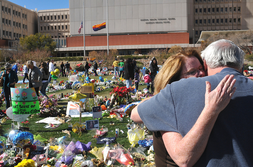 """Mark Kimble, Gabby Giffords Communications Director is hugged by a supporter at the University of Arizona Medical Center two weeks after the January 8th Shooting in NW Tucson. Mark  was standing next to Gabe (Zimmerman who was killed),"""" I will never know why I'm alive and he's dead,"""" said Kimble. In the background is the spontaneous shrine (one of three)) much of it was removed and simply replaced with more. Notes of love, hope, teddy bears and drawings, photographs"""