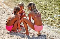 Three little girls playing on the beach in Lefkada, Greece