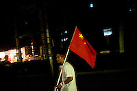 A man carries a Chinese flag through the streets of Nanjing, China, the night before the Olympic Torch Relay arrived in Nanjing.