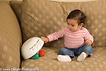 Ten month old baby girl looking for and finding hidden toy, lifting bowl to find toy underneath