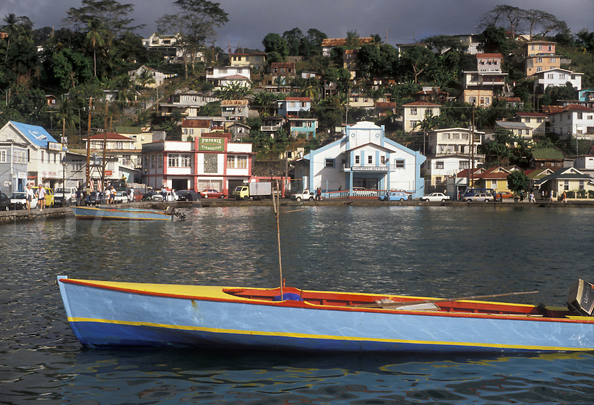 """AJ2523, Grenada, Caribbean, St. George's, Caribbean Islands, Fishing boat anchored on the Carenage Harbor with a view of St. George's the capital of the island of Grenada """"""""the spice isle"""""""" (a British Commonwealth member)."""