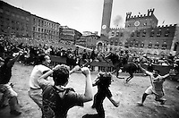 © Francesco Cito / Panos Pictures..Siena, Tuscany, Italy. The Palio. ..Joyful supporters greet the winning horse...Twice each summer, the Piazza del Campo in the medieval Tuscan town of Siena is transformed into a dirt racetrack for Il Palio, the most passionately contested horse race in the world. The race, which lasts just 90 seconds, has become intrinsic to the town's heritage since it was first run in 1597.