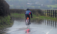 A cyclist makes his way through flood water on Culfor Road in Loughor, Swansea.