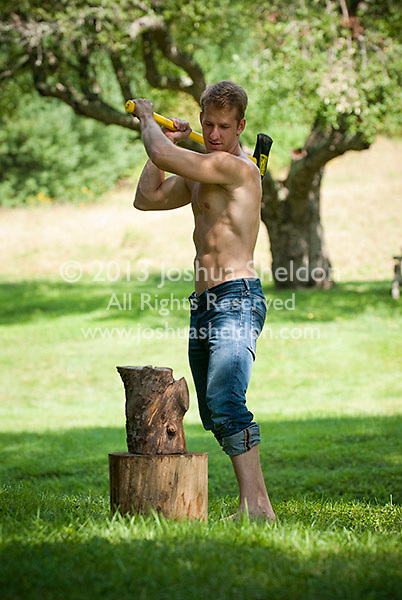 Shirtless man chopping wood with an axe